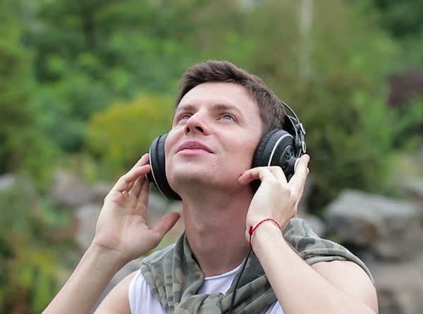 man holding headphones to ears looking skywards